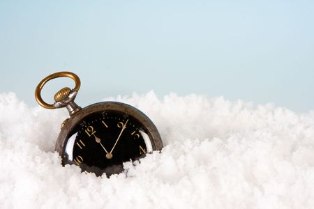 ticking away: Antique watch in the snow ticking away the minutes till new year