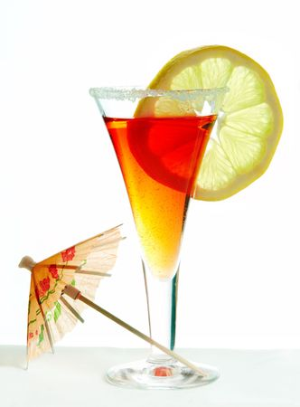 Orange cocktail decorated with lemon slice, sugar and parasol against a white background