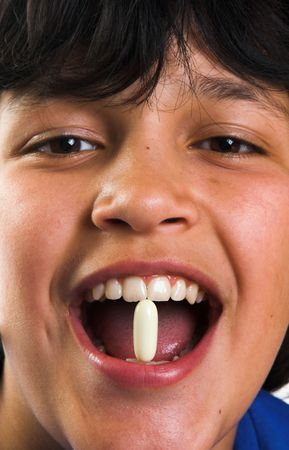 Smiling boy with a pill in his mouth Stock Photo - 3714715