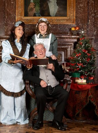victorian fireplace: Vintage christmas scene of a victorian family singing christmas carols.Shot in the antique castle  Stock Photo