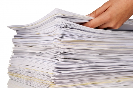 Hand adding more files to a large stack of documents photo
