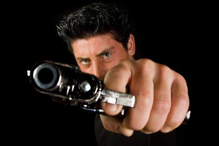 Dark man pointing a gun looking at the camera
