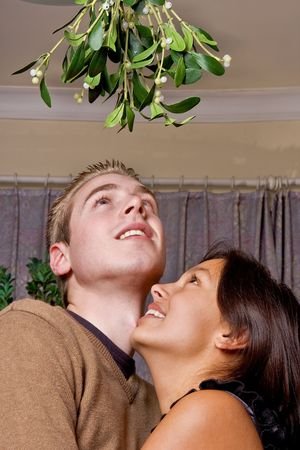 Young couple has just noticed they are standing under a bunch of mistletoe at christmas Stock Photo - 3744552