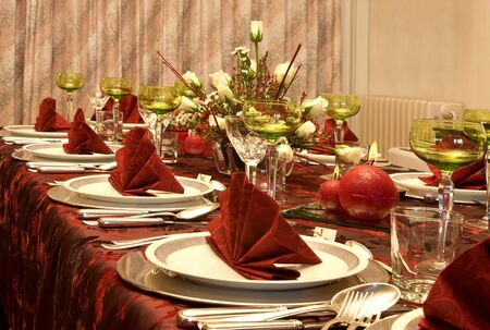 Christmas dinner table with flowers and red napkins Stock Photo
