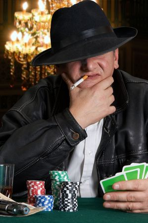 mob: Mafia type with leather jacket playing poker in a classy casino