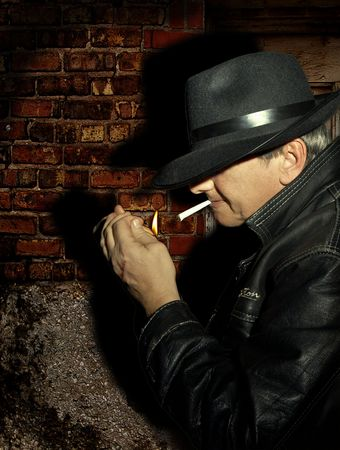 Mysterious man, mafia guy or secret police, waiting in the dark and lighting a cigarette Stock Photo - 3744494