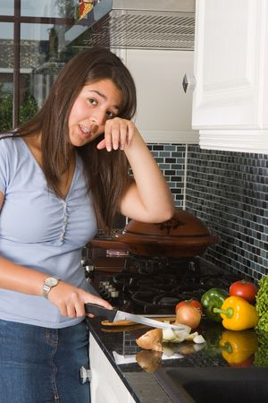 onions: Young woman crying tears while cutting an onion