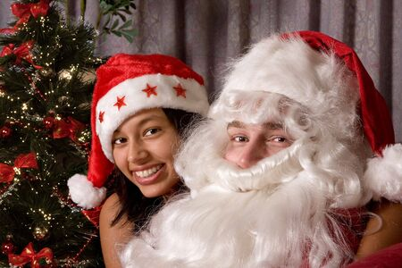 Attractive young woman embracing her boy-friend in santa costume Stock Photo - 3756983