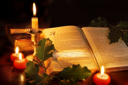 Bible with christmas story lit with candle light