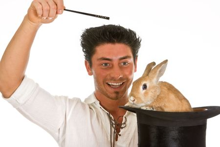 Young man holding a magic wand and a rabbit in a top hat Stock Photo - 3787537