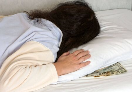 matress: Woman sleeping with money under her pillow during economical crisis