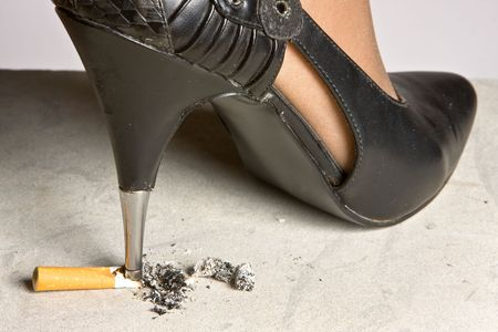 fag: High-heeled stiletto shoe crushing a cigarette on the floor Stock Photo