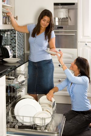 Two friends in the kitchen unloading the dishwasher Stock Photo - 3787553