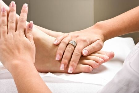 acupressure hands: Womans hands giving a healthy foot massage Stock Photo
