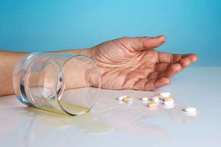 Hand of a person who comitted suicide with sleeping tablets and alcohol Stock Photo - 3835087
