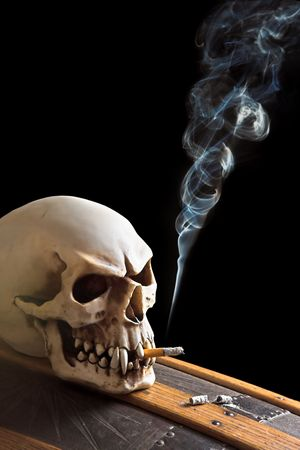 Skull smoking a cigarette, on a coffin Stock Photo