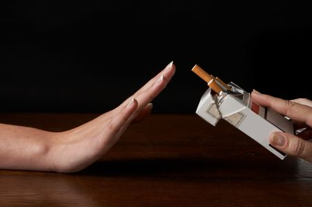 Hand saying no thanks to a packages of cigarettes offered photo