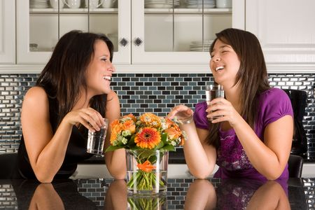 Two friends drinking water in a relaxed moment in the kitchen Stock Photo - 3829713