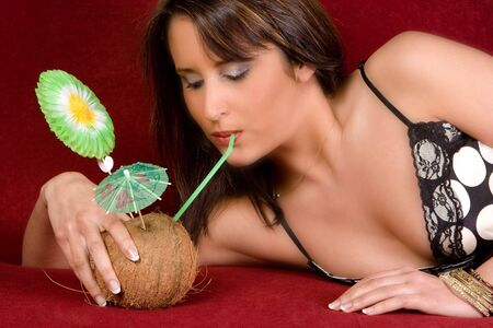 Sexy young woman having a coconut cocktail on a couch Stock Photo - 3858230