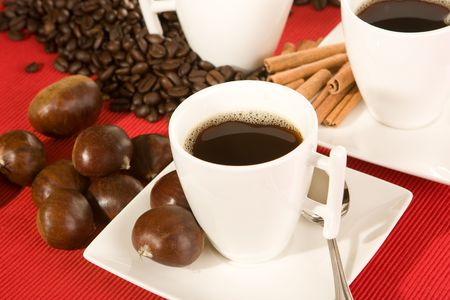 Coffee cup and beans on a red placemat photo