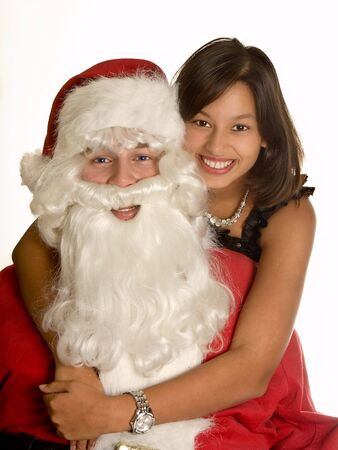 Beautiful young brunette embracing her boy-friend dressed like santa claus with christmas Stock Photo - 3858220