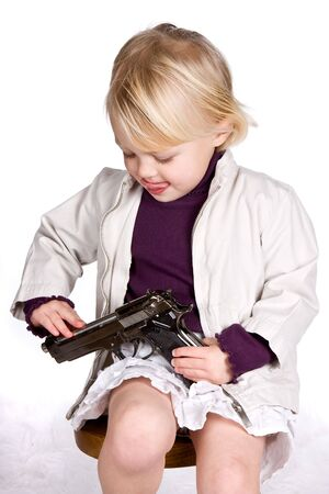 Little innocent girl with her hands on a weapon, playing a dangerous game photo