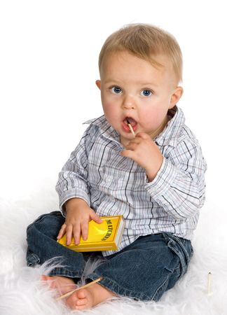 Curious baby playing a dangerous game with matches Stock Photo