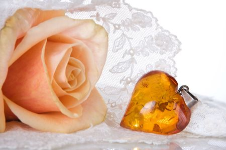amber: Amber heart and roses lying on a lace veil Stock Photo