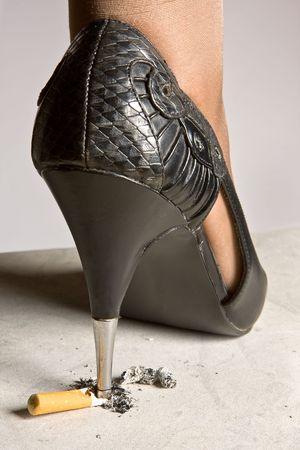 pigiatura: Tacco alto signora scarpa macinazione una sigaretta sul marciapiede