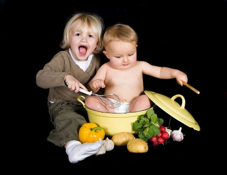 3 years old little girl and her baby brother playing chef together photo