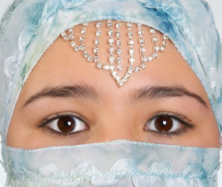 purdah: Beautiful young woman with mysterious eyes, wearing a blue silk veil