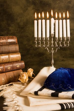 Hanukkah candleholder and jewish prayer shawl, books and cap photo