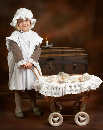 Little girl in Victorian dress, playing with her antique doll Stock Photo - 3921961