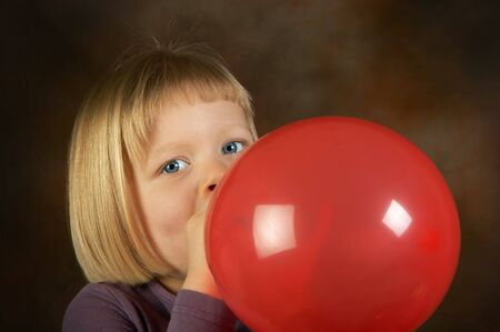 Little girl blowing a red balloon for her birthday party photo