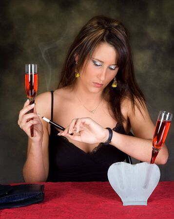 Young sexy woman holding a cocktail looking at her watch Stock Photo - 3921963