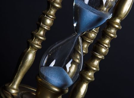 mesure: Bronze hourglass against a black background Stock Photo