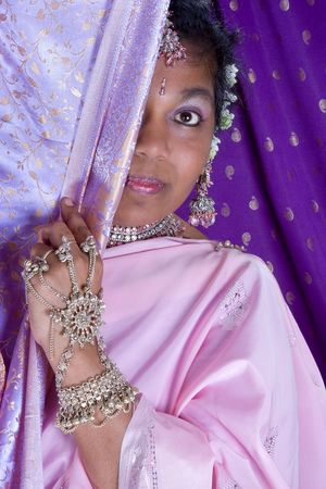Lovely Indian woman wearing a saree, hiding behind a curtain photo