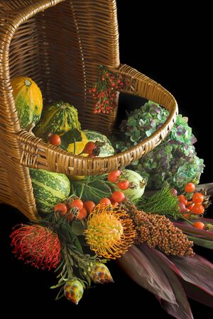 Wicker basket with autumn flowers, berries and gourds photo