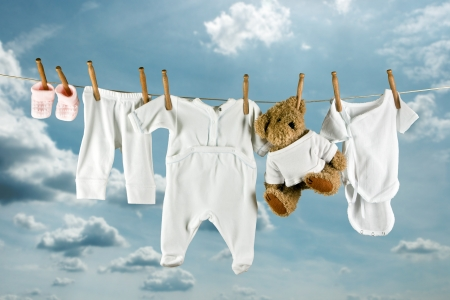 Cute teddy bear hanging outside between baby laundry Stock Photo