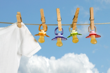 Row of pacifiers hanging next to baby laundry photo