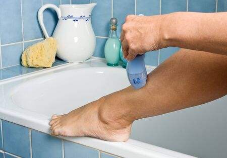 Woman shaving her legs in the bathroom photo