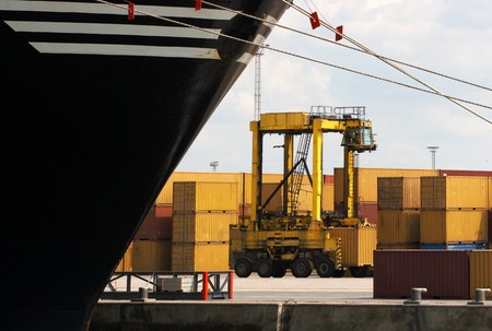 Forklift carrying one single container near a huge container ship (carrying more than 3000) in Antwerp world harbor Stock Photo