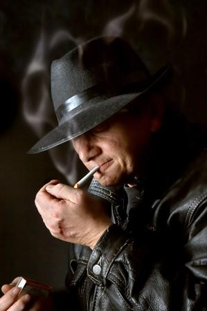 Mafia watchman lighting a cigarette in the dark Stock Photo