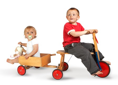 tricycle: Little boy on a tricycle with his sister in a little cart Stock Photo