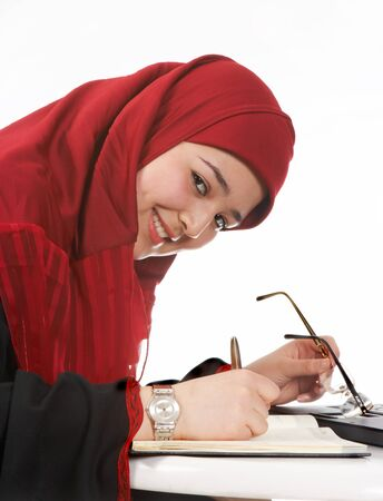 veiled: Young veiled business woman making appointments in her agenda Stock Photo