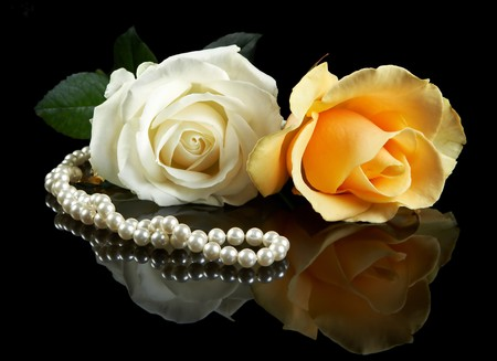 Pearl necklace on a reflective surface, and two beautiful roses Stock Photo