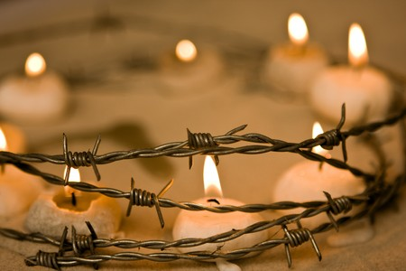 barb: Burning candles in barbed wire, symbol of hope and civil rights