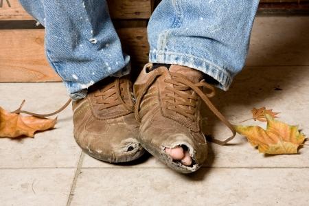Desgastadas y maltratadas zapatos de un mendigo en las calles Foto de archivo