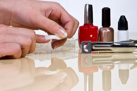 Female hand putting on false nails made of acrylic Stock Photo