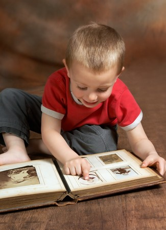 Young boy browsing an antique family album (the faces on the photos in the album cannot be recognized) Stock Photo